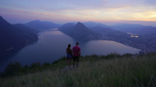 young couple standing together watching sunset over lake and city from mountain top - ticino canton stock videos and b-roll footage