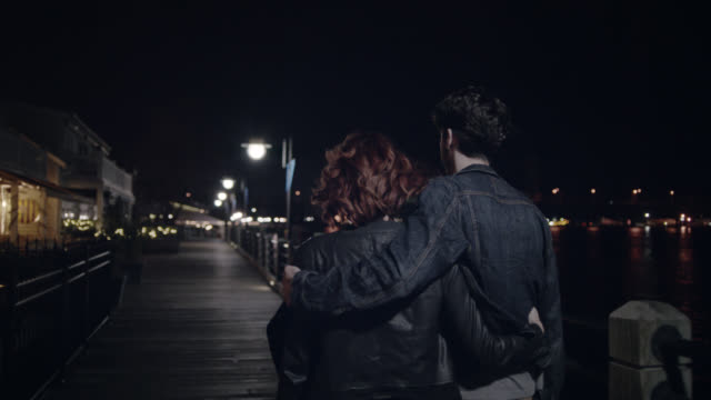 ws slo mo. young couple stroll down waterfront boardwalk at night. - romance stock videos & royalty-free footage
