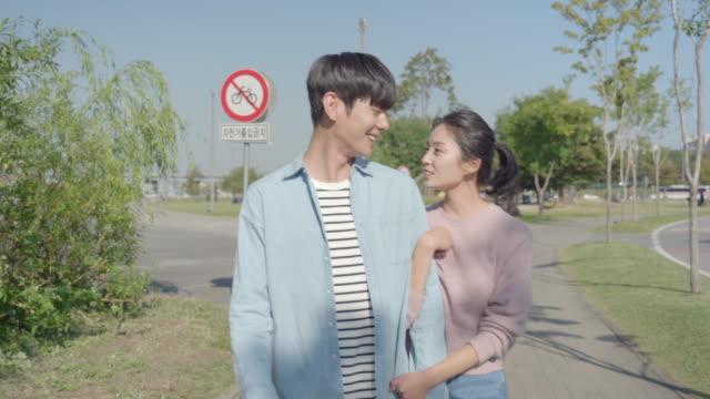 vídeos de stock, filmes e b-roll de young couple strolling across the han river park - de braços dados