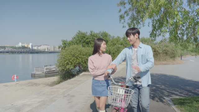 young couple strolling along the han river park with a bicycle - south korea couple stock videos & royalty-free footage