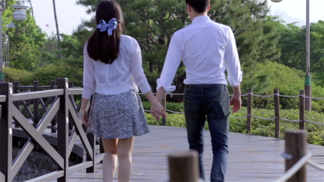 Young couple strolling and holding their hands in a park and then the man embracing the woman
