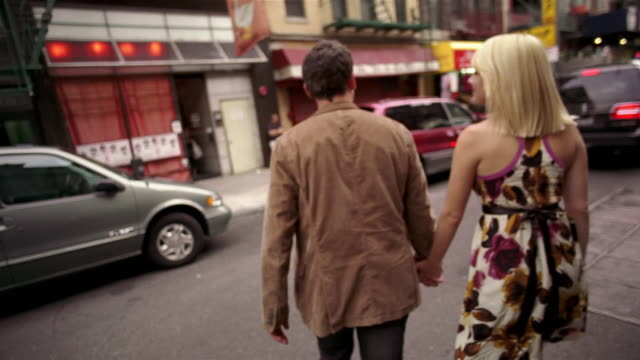 SLO MO, MS, Young couple strolling in Chinatown, rear view, New York City, New York, USA