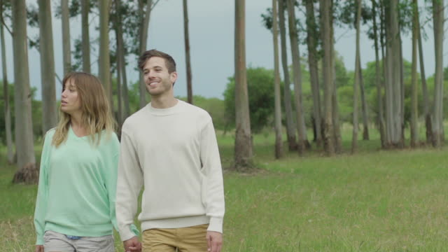 young couple strolling together outdoors - gemeinsam gehen stock-videos und b-roll-filmmaterial