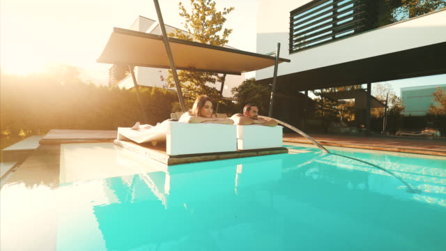 young couple sunbathing by swimming pool. - sunbed stock videos & royalty-free footage