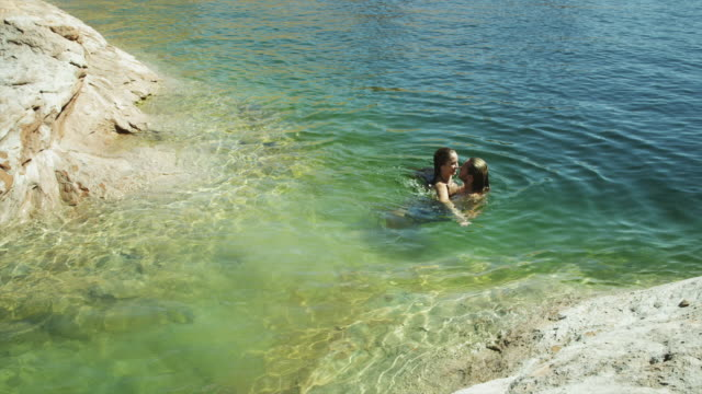 ws ha young couple swimming in lake powell / utah, usa - lake powell stock videos and b-roll footage