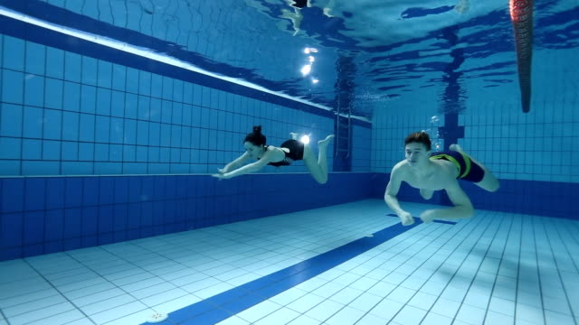 Young couple swimming underwater in pool