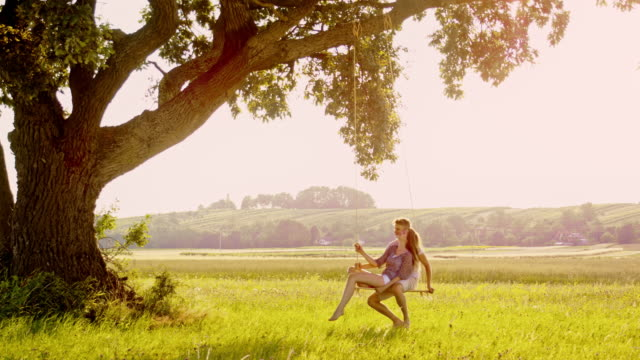 SLO MO Young couple swinging on a tree swing in nature