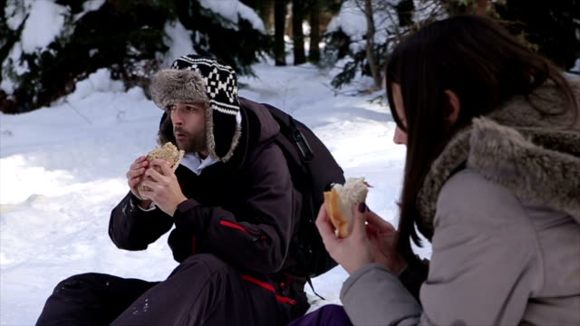 Young couple take a break in skiing, eat sandwiches