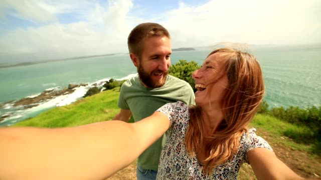young couple take a selfie portrait over grassy coastline hill - cliff stock videos & royalty-free footage