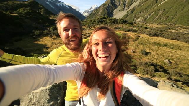 Young couple take self portrait on mountain background