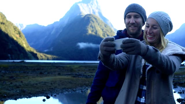 young couple take selfie portrait in milford sound, nz - tourism stock videos & royalty-free footage