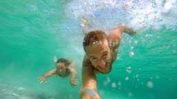 Young couple take selfie portrait underwater with action camera