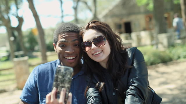 Young couple take selfie with smartphone in public park