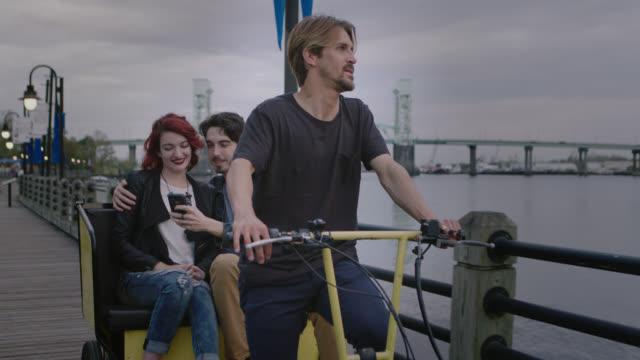 vidéos et rushes de ws slo mo. young couple take selfies riding in bike taxi on riverfront boardwalk. - allée couverte de planches