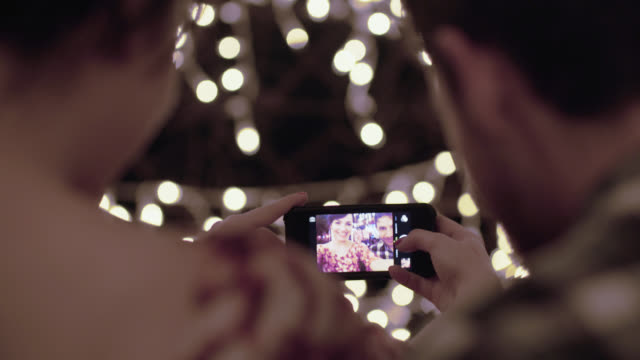 young couple take selfies together under christmas lights on a caf_ patio - over the shoulder stock videos & royalty-free footage
