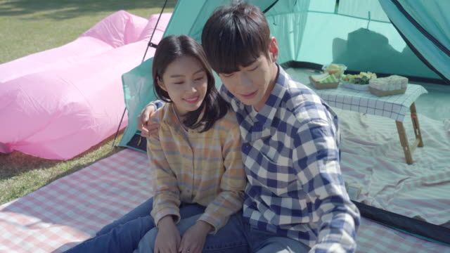 young couple taking a photo with a polaroid camera in front of a tent in the han river park - polaroid camera stock videos & royalty-free footage