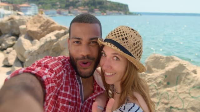 vídeos de stock, filmes e b-roll de jovem casal tomando uma selfie à beira-mar - casal jovem