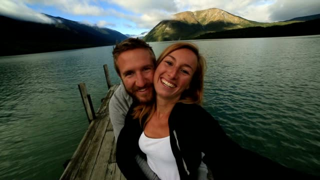 Young couple taking a selfie on a wooden jetty