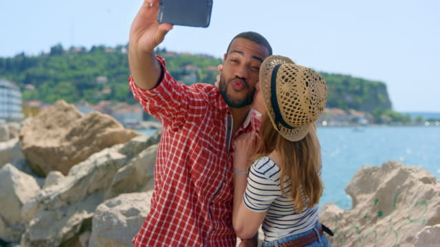 Young couple taking a selfie with a kiss by the sea in sunshine