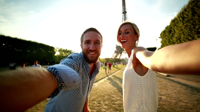 Young couple taking selfie at the Eiffel tower-Paris POV