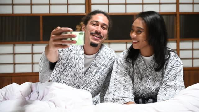 stockvideo's en b-roll-footage met jong stel neemt selfie in bed in traditionele japanse ryokan - ryokan