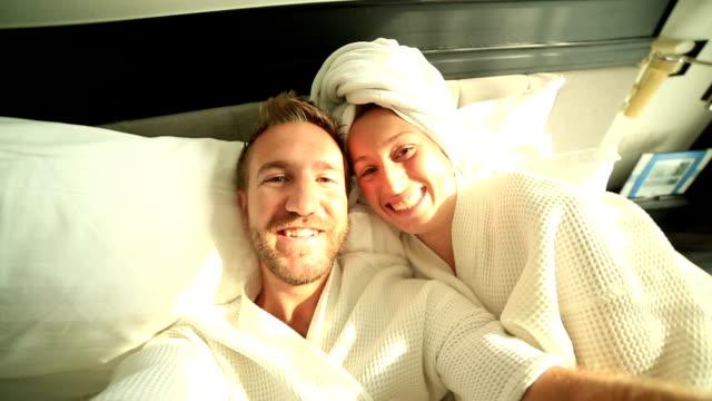 Giovane coppia prendendo selfie in hotel letto
