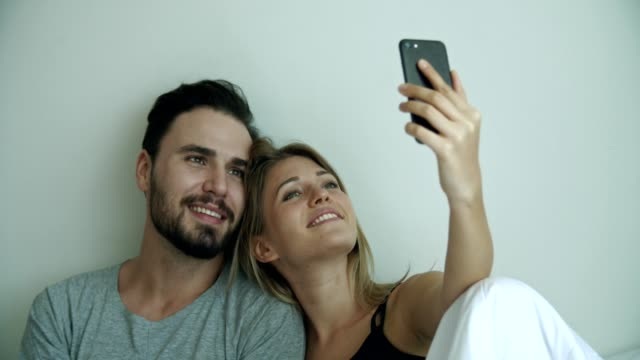 young couple taking selfie on phone camera - resting stock videos & royalty-free footage