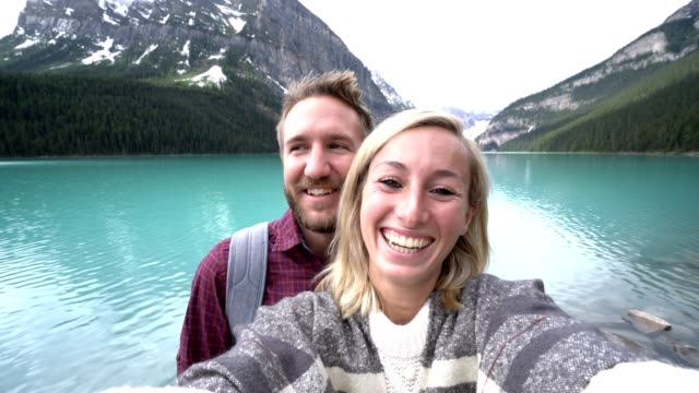 young couple taking selfie portrait at lake louise - banff national park stock videos & royalty-free footage