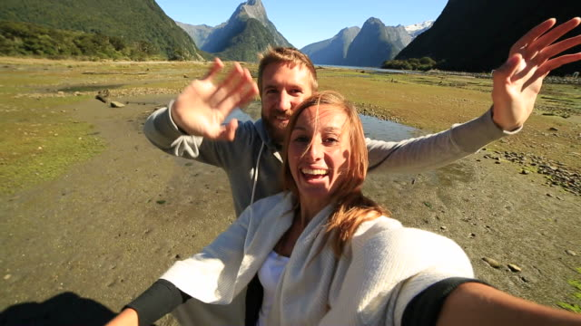 Young couple taking selfie portrait at Milford Sound