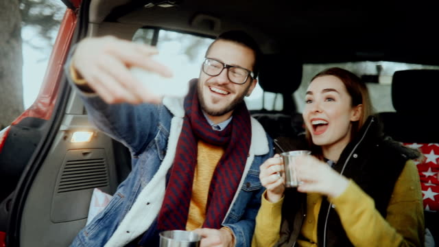 若い彼らの車の後ろにリラックスしながらの撮影 selfie をカップルします。 - 座る点の映像素材/bロール