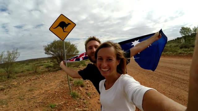 young couple taking selfie with kangaroo sign, australia - road warning sign stock videos & royalty-free footage