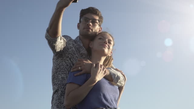 young couple taking selfies in the sunshine - southern european stock videos & royalty-free footage