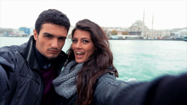 young couple taking selfies near the sea in city - golden horn istanbul stock videos and b-roll footage