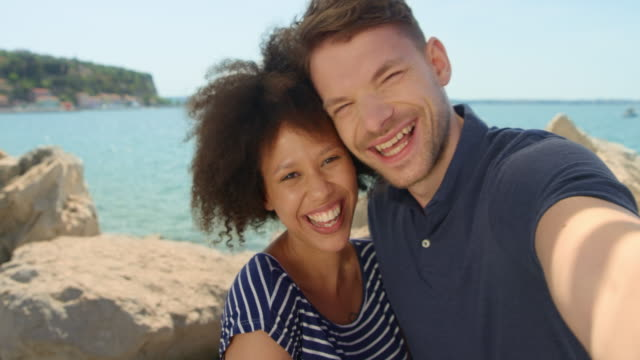 Young couple taking selfies standing on the walkway by the sea in sunshine