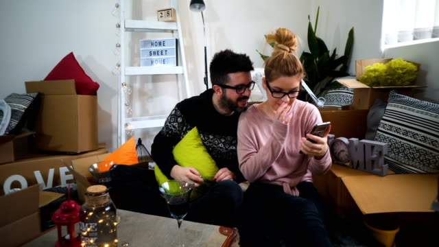 young couple taking selfies with her smartphone in their new home - relocation stock videos & royalty-free footage