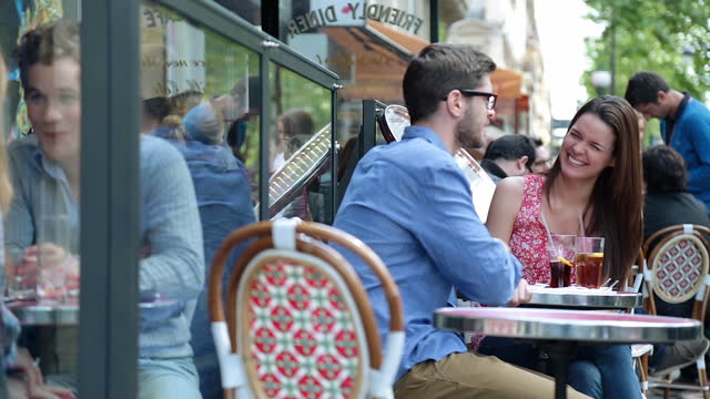 Young couple talk and laugh at quaint sidewalk cafe on the Boulevard Saint-Germain in Paris.