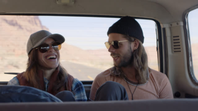 vídeos de stock e filmes b-roll de young couple talk and laugh in back of vehicle on moab road trip. - cultura jovem