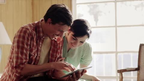 vídeos y material grabado en eventos de stock de young couple talk and laugh while browsing tablet computer on motel bed - en búsqueda