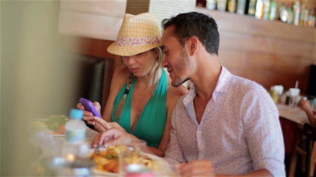 Young couple talk and text over lunch at Brazilian restaurant