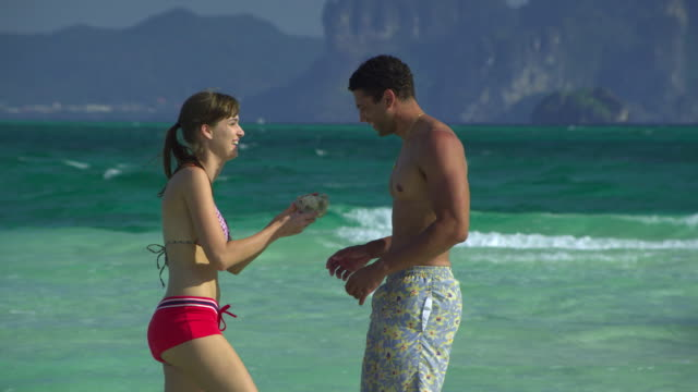 stockvideo's en b-roll-footage met ms young couple talking and looking at coral on tropical beach, krabi, thailand - zwembroek