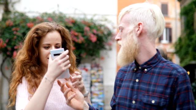 若いカップルが話し、路上で写真を撮る - ラツィオ州点の映像素材/bロール