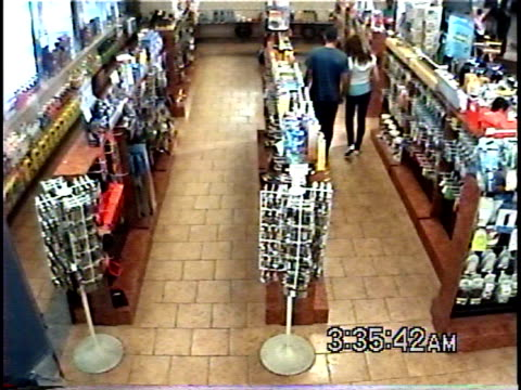HA WS Young couple talking, holding hands, and hugging in convenience store / Brooklyn, New York, USA