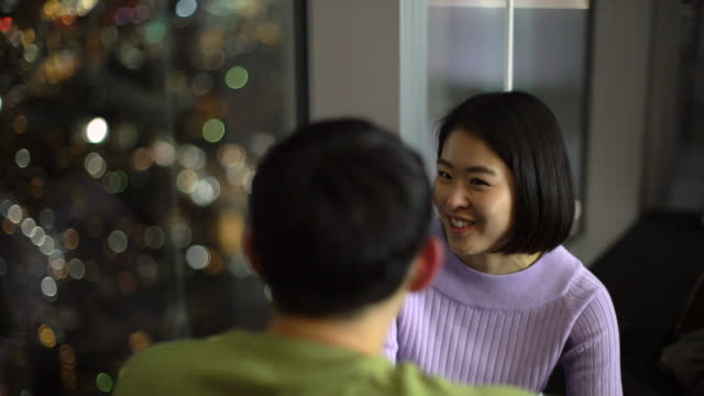 CU young couple talking near a window at night