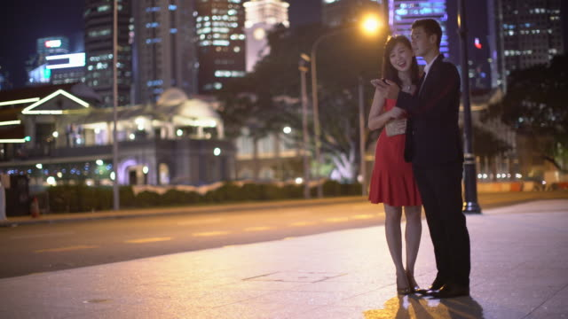 WS Young couple talking together at night in the city.