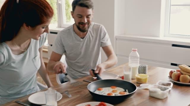 vídeos de stock e filmes b-roll de young couple talking while having a breakfast together in the morning. - servir comida e bebida