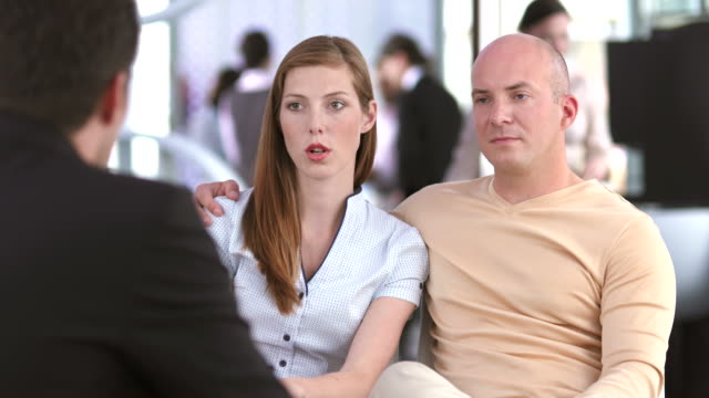 hd dolly: young couple talking with bank teller - banking stock videos & royalty-free footage