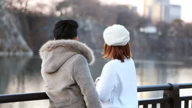 young couple talking with romance sunset on the lake together in public park at osaka, japan - only japanese stock videos & royalty-free footage