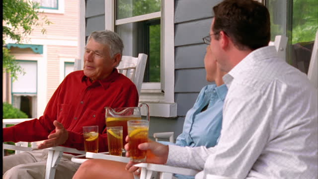a young couple talks with a retiree on his front porch. - neighbour stock videos and b-roll footage
