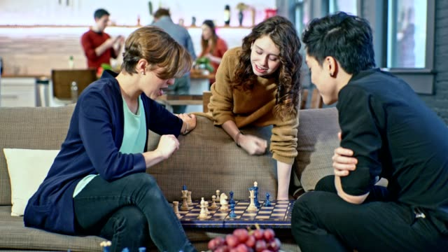 Young couple, the Caucasian girl and the Asian guy, playing chess game on the coach in the living room, when teenager girl, probably the younger sister, giving some advice about the game. Same time, group of people in the backdrop cooking in the kitchen.
