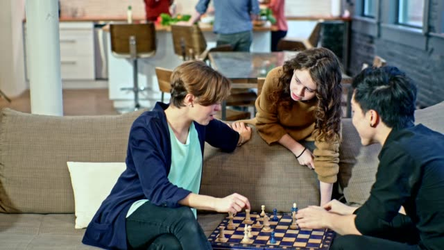 young couple, the caucasian girl and the asian guy, playing chess game on the coach in the living room, when teenager girl, probably the younger sister, giving some advice about the game. same time, group of people in the backdrop cooking in the kitchen. - little girls giving head stock videos and b-roll footage